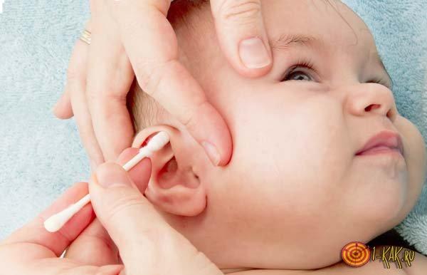 Младенцу проводят гигиеническую процедуру слуховых органов