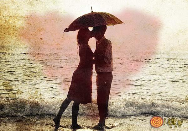 Влюбленные под зонтом на закате у моря