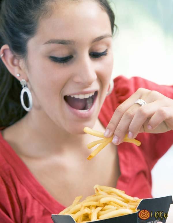 Девушка ест жареный картофель