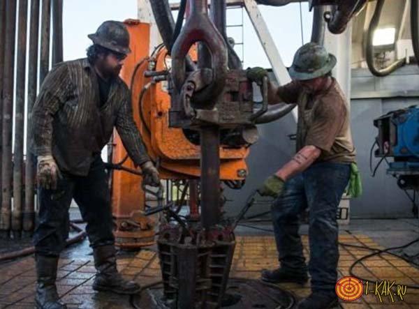 Рабочие добывают нефть