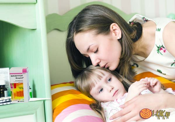 Мать целует больного ребенка в лобик