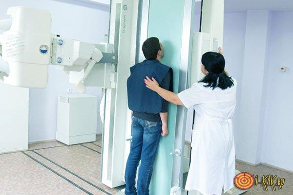 Делает снимок рентгена в кабинете