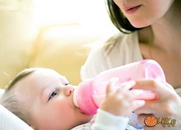 Кормящая мама дает детское питание малышу
