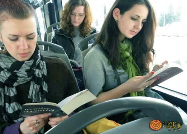 Две девушки читают книгу в транспорте