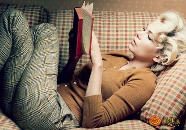 Читает книгу на диване