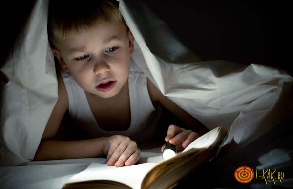 Мальчик читает в темноте под одеялом