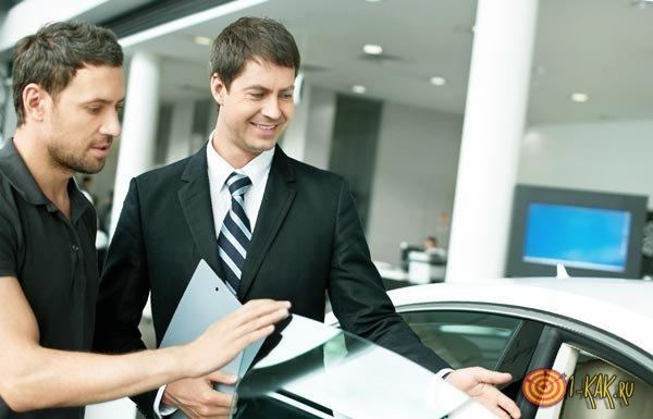 Менеджер по продажам показывает автолмобиль