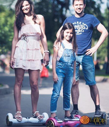 Семья едет на гироскутере в парке