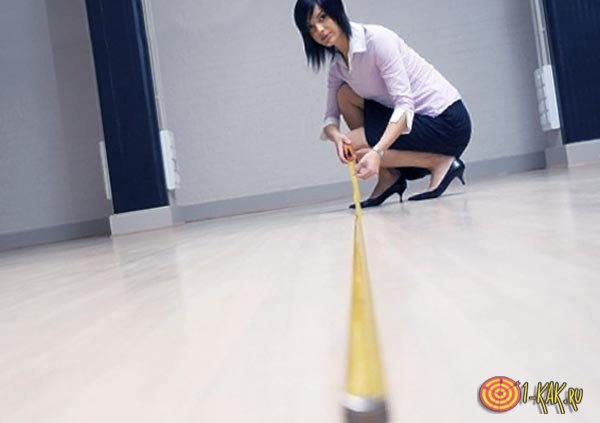 Девушка измеряет площадь в квадратах