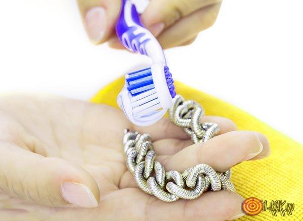 Чистит украшения зубной щеткой