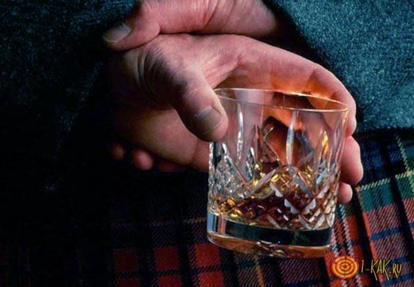 Шотландец пьет виски в стакане