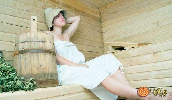 Беременная сидит в сауне