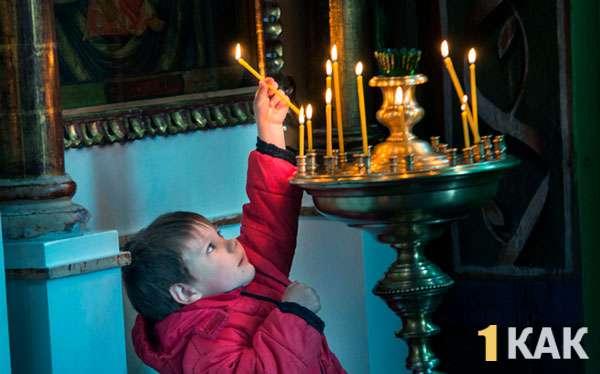 Мальчик тянется к подсвечникам в церкви